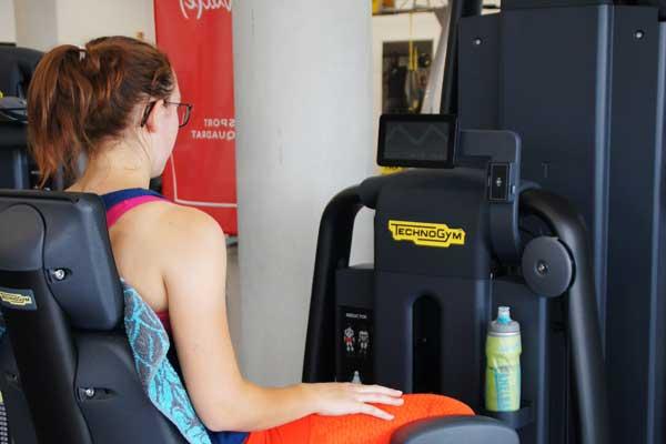 Junge Dame beim Training am TechnoGym Gerät im Trainingsbereich