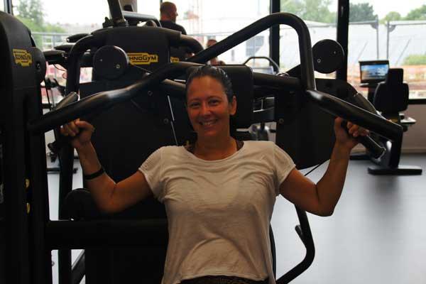 Fröhliche Dame beim Training im TechnoGym Gerätepark